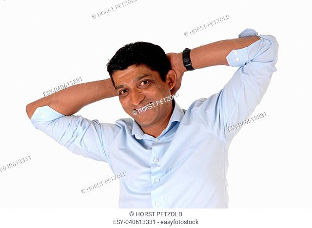 A smiling East Indian man in closeup standing in a blue shirt with his.hands behind his head, isolated for white background