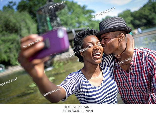 Young couple taking selfie with smartphone, Bethesda fountain, Central Park, New York City, USA
