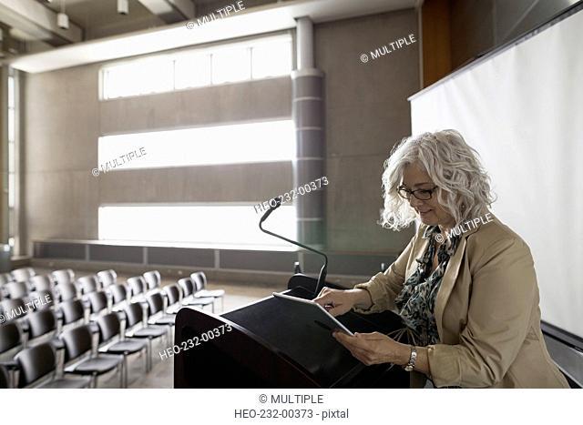 Woman with digital tablet at podium empty auditorium
