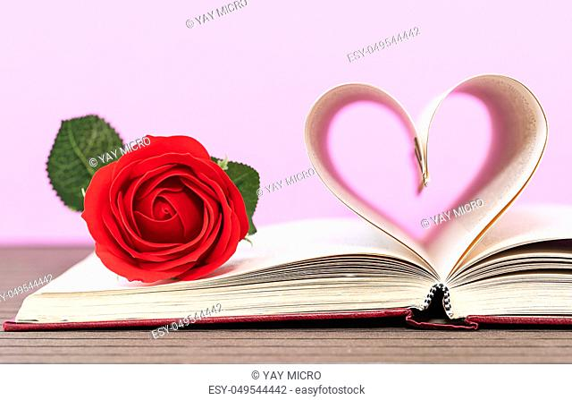 Pages of book curved into a heart shape and red rose. Love concept of heart shape from book pages on pink background