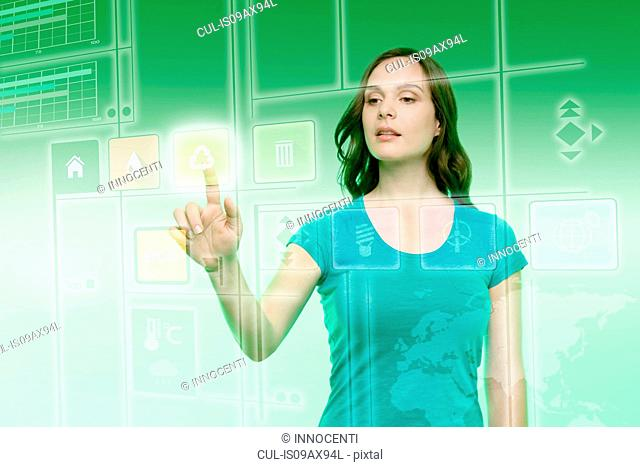 Young woman touching recycling icon on graphical screen