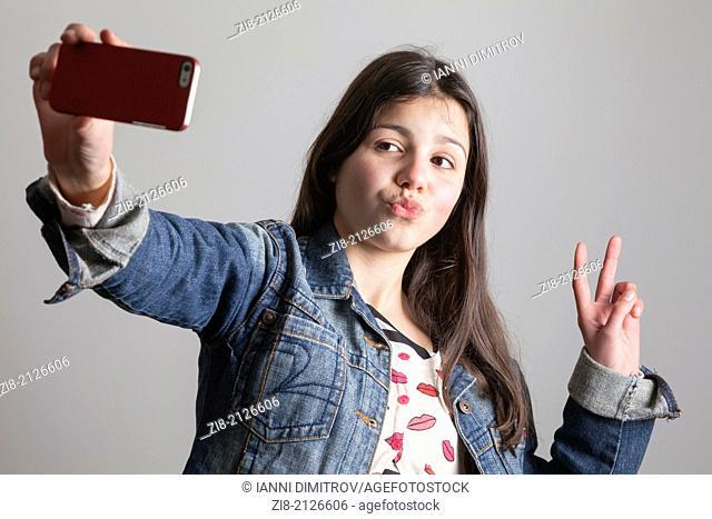 Teenage girl takes a selfie on camera phone