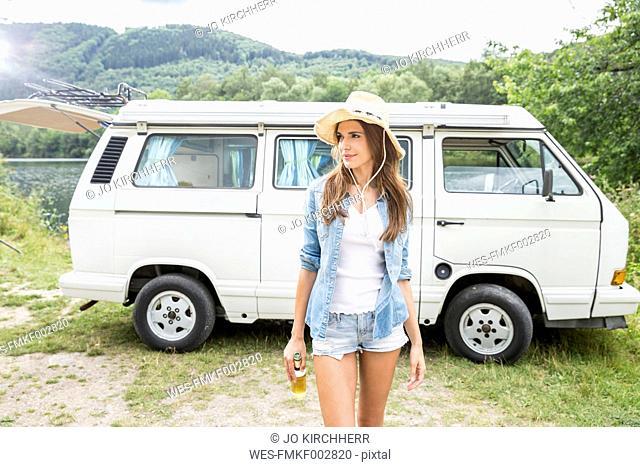 Woman wearing hat walking with beer bottle beside van