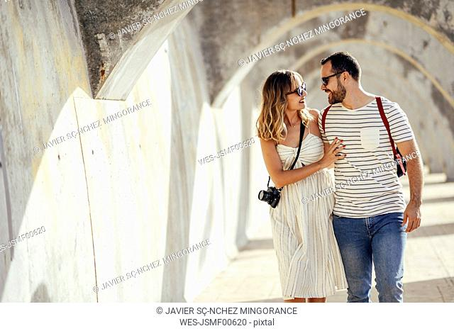 Spain, Andalusia, Malaga, happy tourist couple walking under an archway in the city