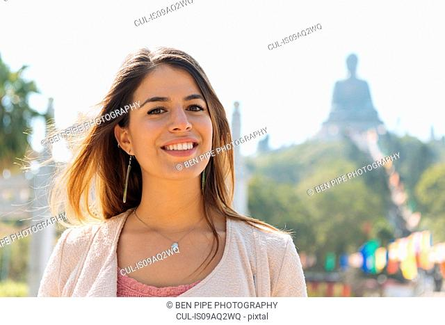 Portrait of young female tourist in front of Tian Tan Buddha, Po Lin Monastery, Lantau Island, Hong Kong, China