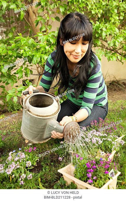 Woman watering flowers outdoors