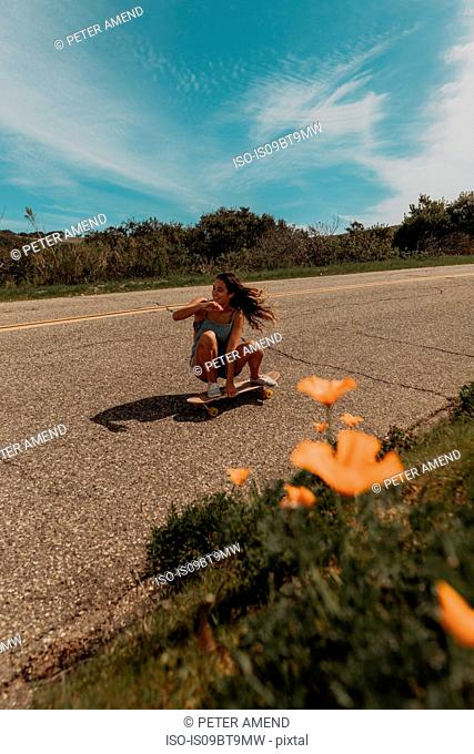 Young female skateboarder crouch skateboarding along rural road, Jalama, California, USA