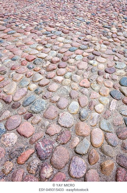 Old European rounded cobblestones of various shapes and sizes in perspective