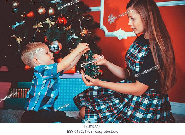 Young mother and her son near a Christmas tree in the decorated room with gifts