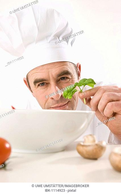 Cook putting a basil leaf into a porcelain bowl