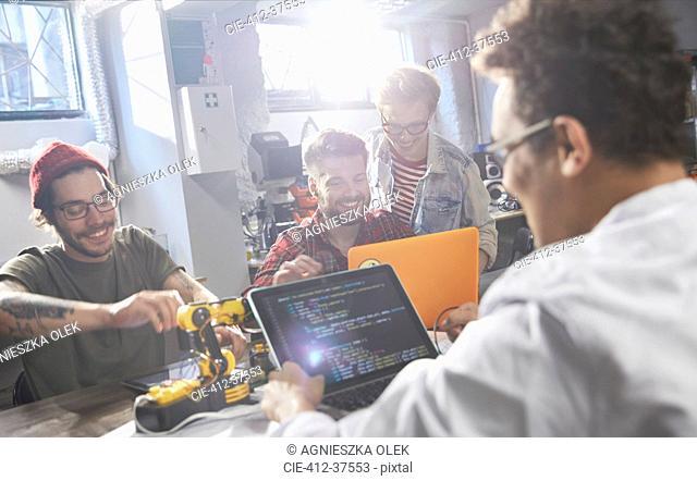 Computer programmers programming robotics in workshop