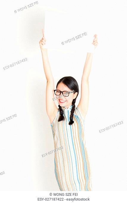 Portrait of young Asian woman in traditional qipao dress hand holding white blank paper card, celebrating Chinese Lunar New Year or spring festival
