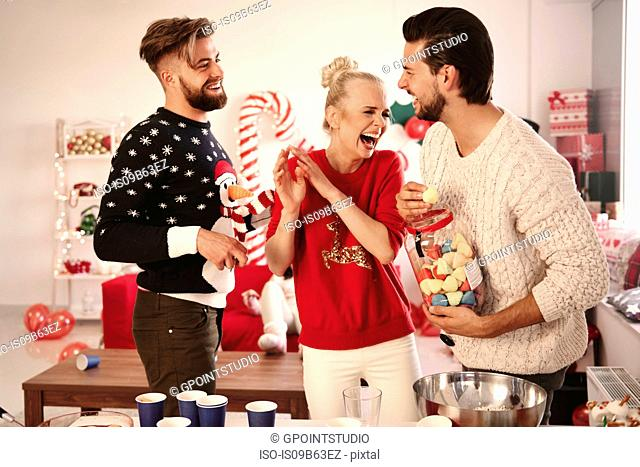 Three young friends laughing at christmas party