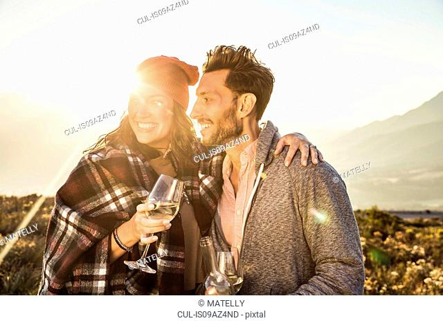 Couple in field holding wine glasses looking away