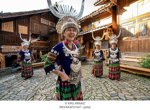 China, Guizhou, happy Miao women wearing traditional dresses and headdresses standing on village square