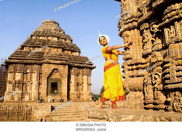 Odissi dancer strike pose re-enacts Indian myths such as Ramayana in front of world heritage Sun temple complex in Konarak , Orissa , India MR400