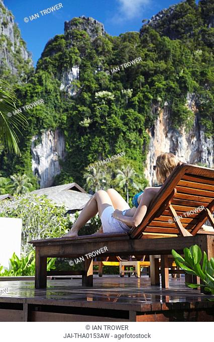 Woman sitting on sun lounger by pool in Bhu Nga Thani Resort and Spa, Railay, Krabi Province, Thailand MR