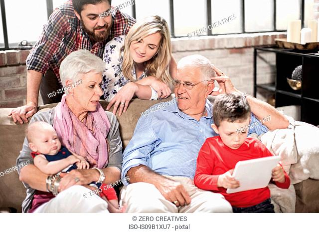 Three generation family using digital tablet at home