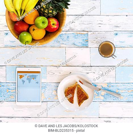 Breakfast and digital tablet on white wooden table