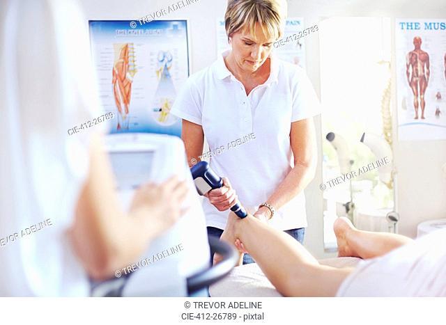 Physical therapist using ultrasound probe on woman's leg