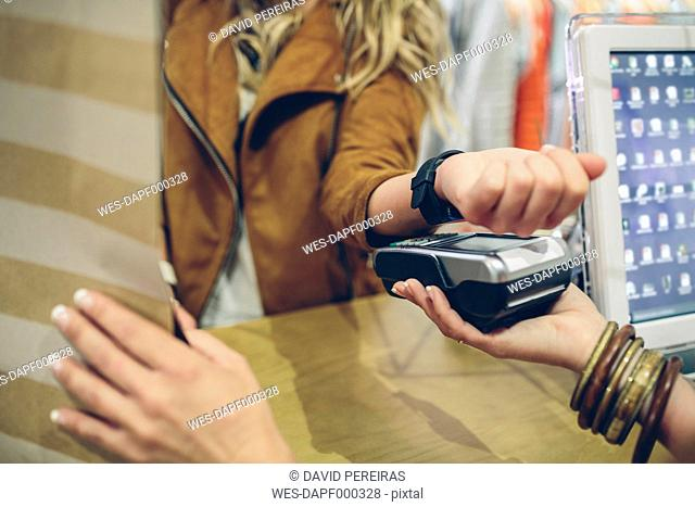 Woman paying using smartwatch with NFC technology in a store