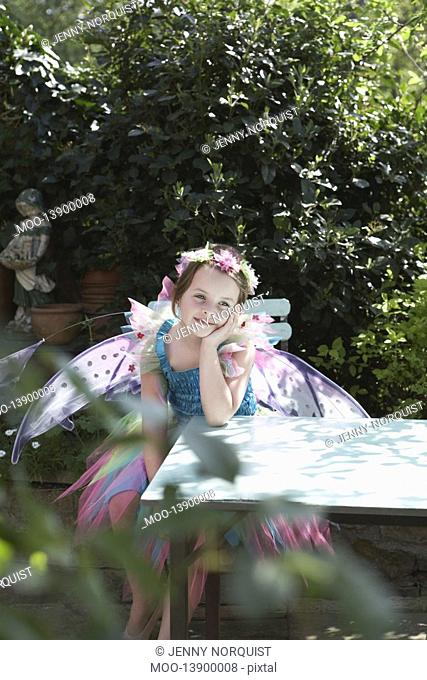 Portrait of young girl 5-6 in fairy costume sitting at garden table