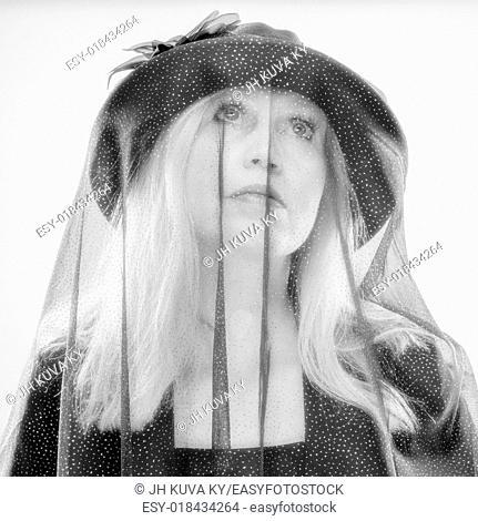 Widow, mature woman wearing black costume and veil, studio shot