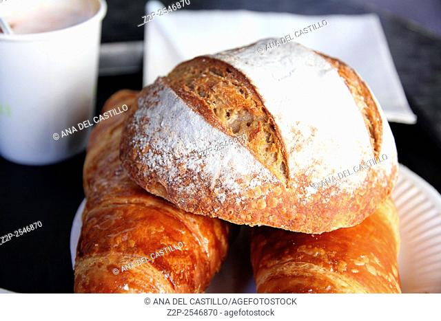 Two croissants and bread with coffee, breakfast table