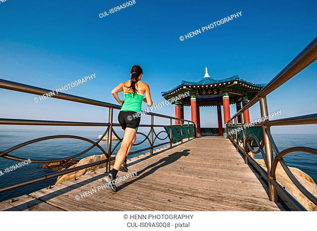 Mature woman running towards the sunrise pavilion, Sokcho, Gangwon, South Korea