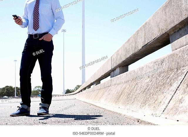 Businessman on cell phone on city street