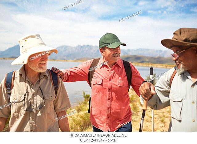 Active senior men friends hiking at sunny lakeside