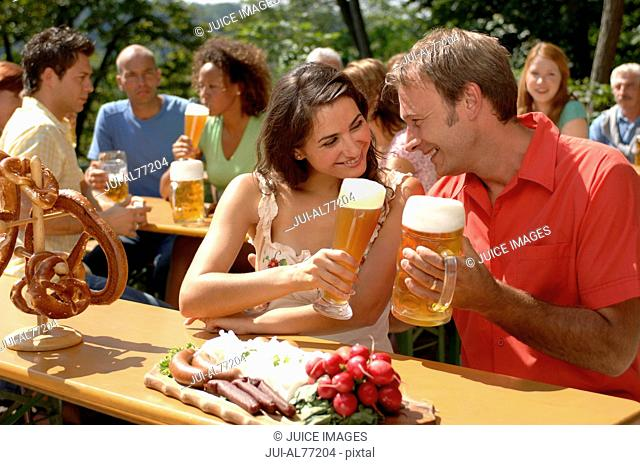 View of a young couple toasting each other, beergarden, Munich, Bavaria, Germany