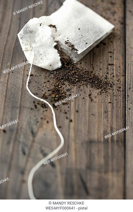 Torned tea bag and black tea scattered on wood