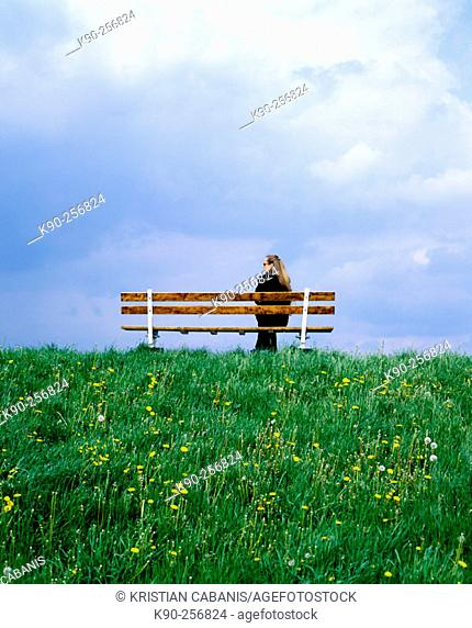 Woman sitting on bench during upcoming rain. Altes Land, Lower Saxonia. Germany