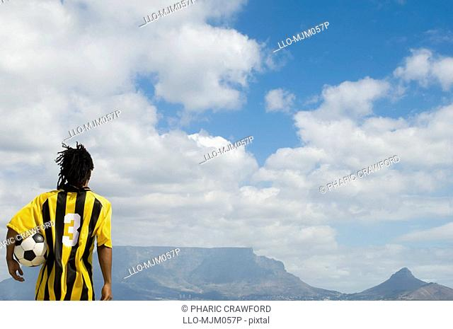 Soccer player holding soccer ball under arm looking at Table Mountain, Table View, Cape Town, Western Cape Province, South Africa