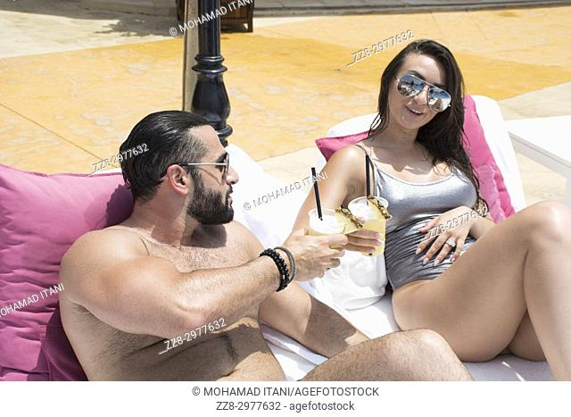 Couple drinking cold beverage by the swimming pool