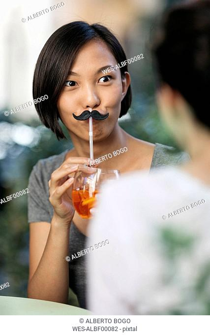 Portrait of young woman with toy moustache and cocktail at sidewalk cafe with her friend
