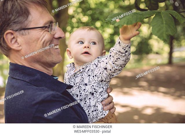 Smiling father holding baby boy at a tree