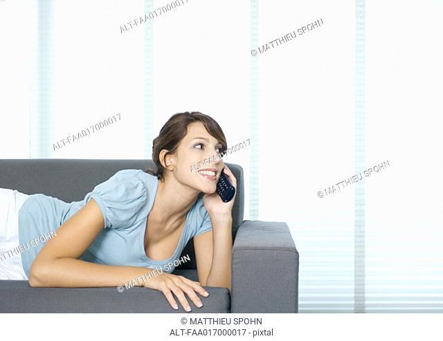Young woman lying on couch, using cell phone