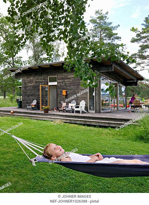 Sweden, boy (6-7) lying on hammock in front of summer house
