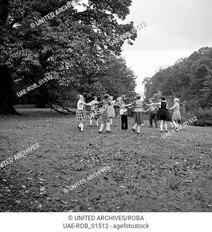 Kinder spielen Ringelrein in einem Park, Hamburg 1954. Children playing ring-a-ring-a-roses at a park in Hamburg 1954