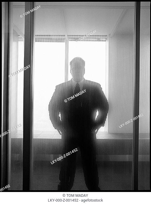 Man in suit behind frosted glass