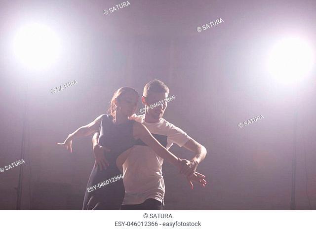 Young couple dancing latin music: Bachata, merengue, salsa. Two elegance pose on white room