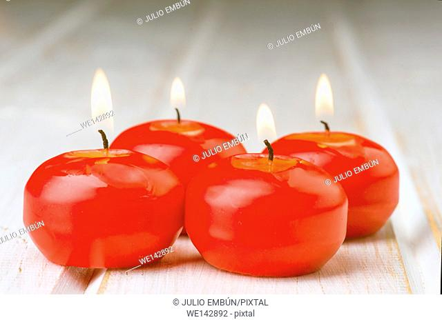 red lighted candles on white wood