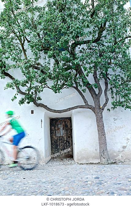 Female cyclist passing an old castle tower door, Burghausen, Chiemgau, Bavaria, Germany