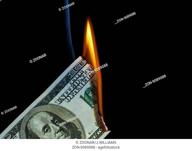 Smoke and fire rises from a burning 100 dollar USA American dollar note. Black background with copy space area for finance related wealth designs and ideas