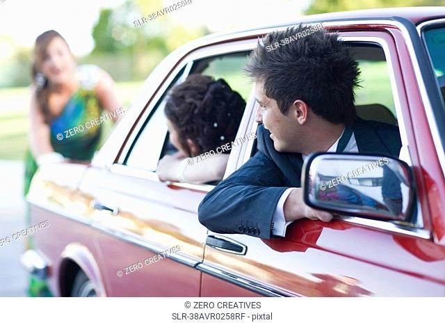 Teenage girl in gown pushing car