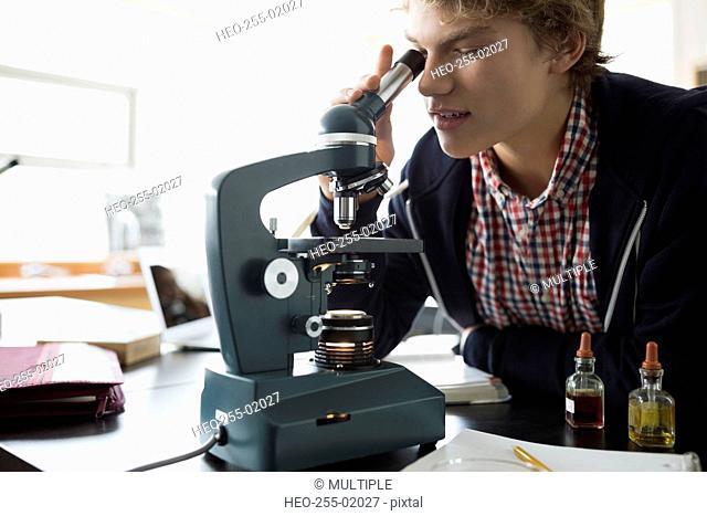 High school student using microscope science laboratory classroom