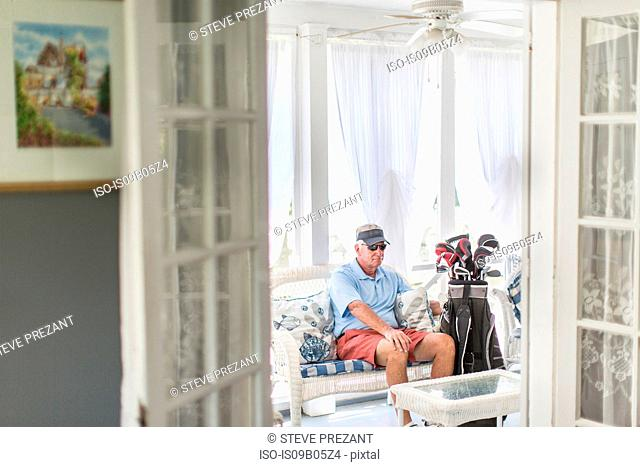 Senior male golfer sitting through conservatory doorway with golf bag