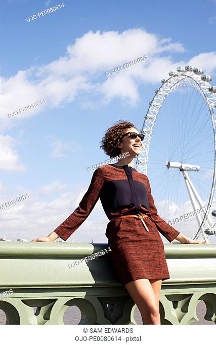Smiling woman leaning on railing of bridge in front of ferris wheel